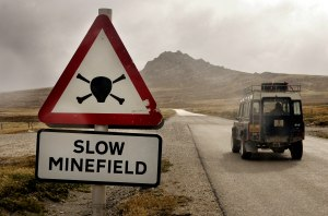 STANLEY, FALKLAND ISLANDS - FEBRUARY 06: (EDITOR'S NOTE RAIN ON CAMERA LENS) A Landrover vehicle passes a road sign warning drivers to slow down for a minefield on February 6, 2007 near Stanley, Falkland Islands.  (Photo by Peter Macdiarmid/Getty Images)
