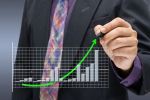Businessman writng arrow on success graph